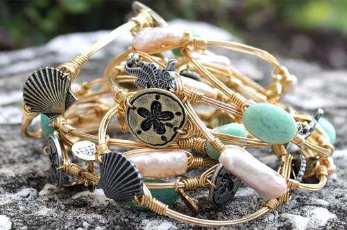 Gold plated bangle features starfish and shells.