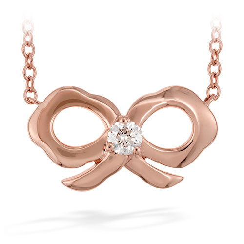 A cute little diamond is in the middle of this rose gold bow pendant.